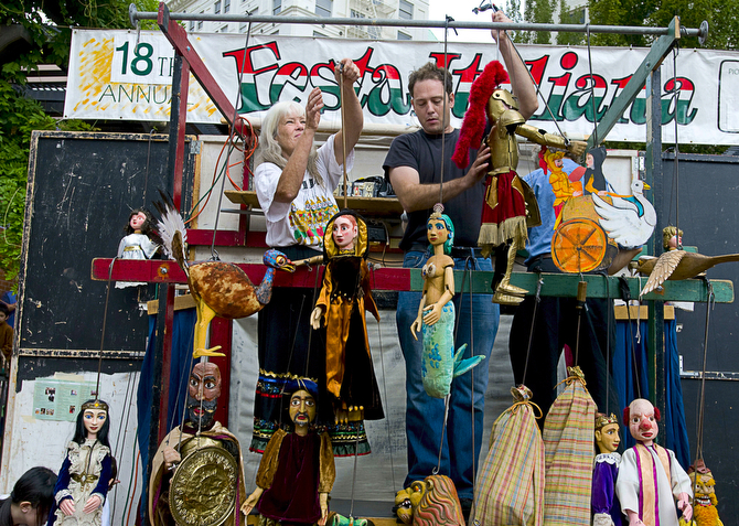 Chris Carter, left, and Dmitri Carter, her son, quickly change puppets during a performance at Festa Italiana. (Benjamin Brink/The Oregonian)